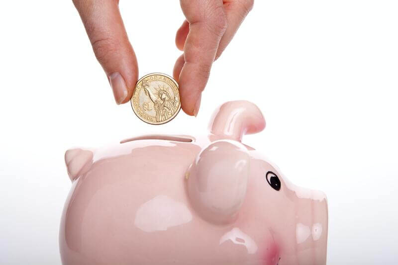 豚の貯金箱へコインを入れる
