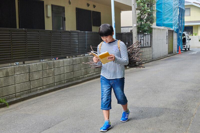 歩きながら読書する少年